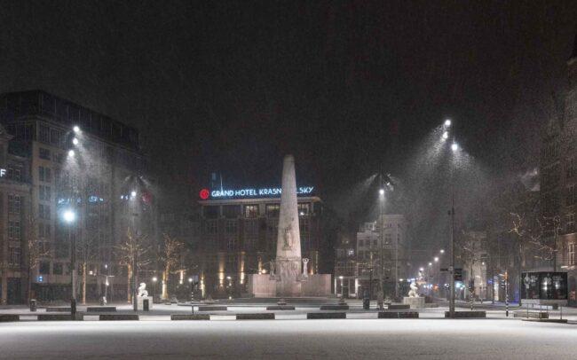 Avondklok Amsterdam sneeuw corona Monument Dam