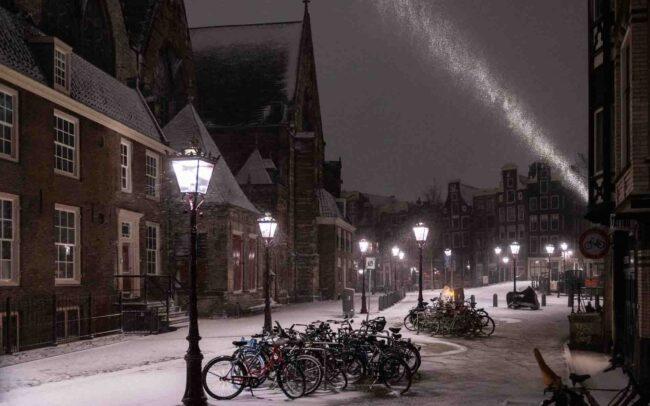 Avondklok Amsterdam sneeuw corona Oudekerksplein Wallen