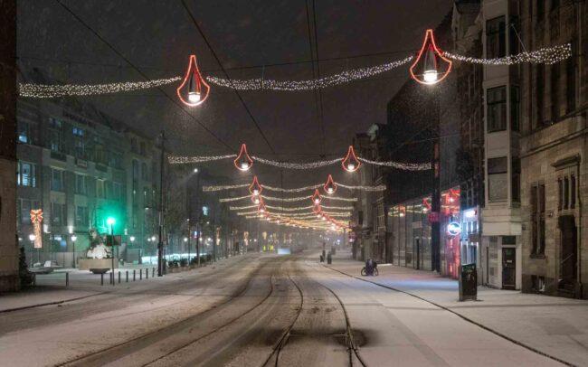 Avondklok Amsterdam sneeuw corona Rokin